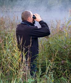 Man Using Binocular in a field with fog