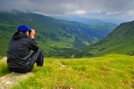 Young Man Viewing Valley with Binocular
